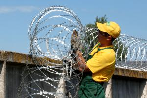 Установка заграждения Гюрза на забор из бетонных плит